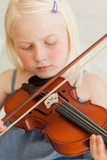 A girl plays the violin sweetly as she closes her eyes