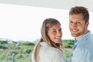 Man and woman smile as they look back at the camera