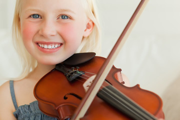 A smiling young girl plays the violin