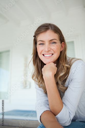 A woman with her hand on her chin smiles as she looks ahead