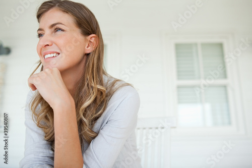 Woman with a hand on her chin looks slightly up