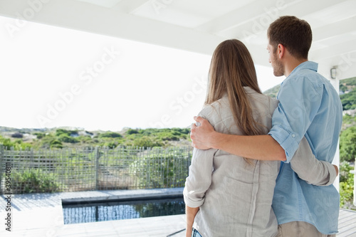 An embracing couple look out from their porch at a swimming pool