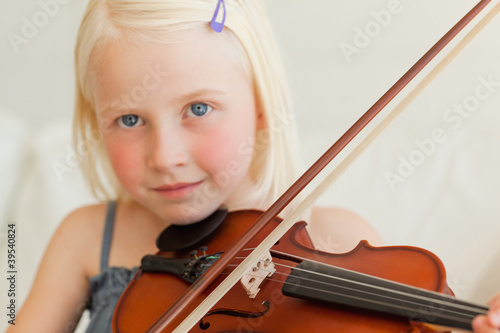A girl looking ahead as she plays the musical instrument