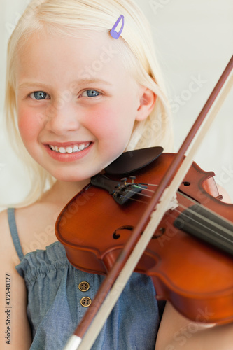 A smiling girl looks forward as she plays