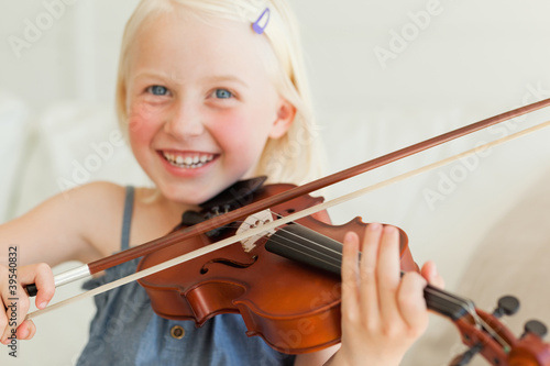 A cute girl enjoys playing the violin