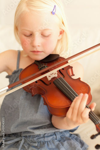 Sweet young girl softly plays the violin