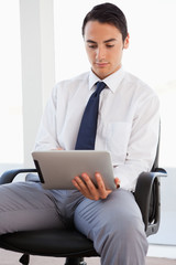 Businessman using a touchpad while sitting