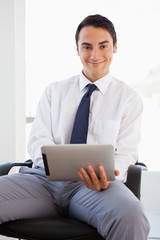 Portrait of a businessman using a touchpad while sitting