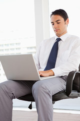 Businessman using a laptop on his knees