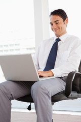 Smiling businessman using a laptop on his knees