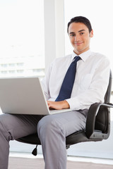 Portrait of a businessman using a laptop on his knees