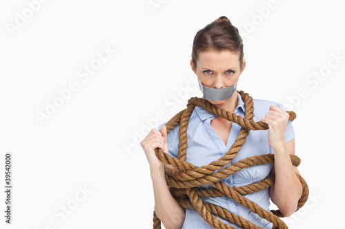 Businesswoman trying to untie herself
