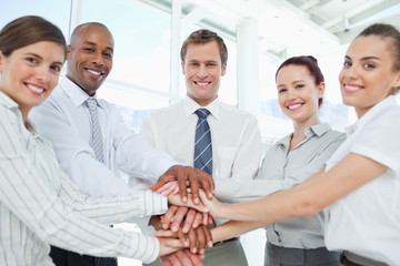 Smiling businessteam doing teamwork gesture