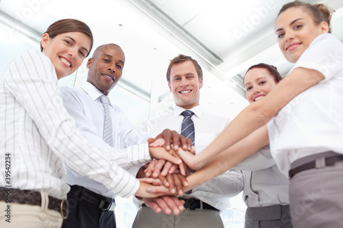 Smiling salesteam putting their hands together for a teamwork gesture