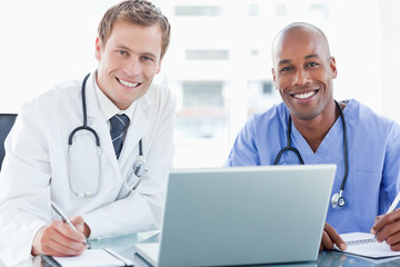 Smiling doctors with laptop