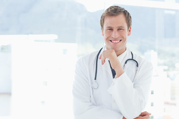 Smiling doctor standing next to a window