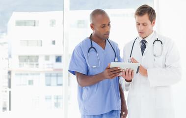Standing doctors using tablet