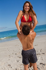 Portrait of a woman in swimsuit being raised by her boyfriend