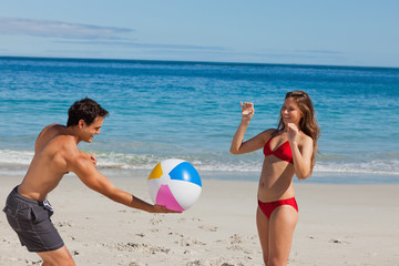 Attractive couple playing with a ball