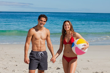 Portrait of an attractive couple holding a beach ball