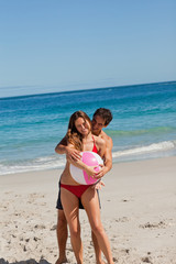 Man embracing his girlfriend holding a beach ball