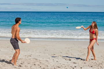 Young couple playing with beach racket