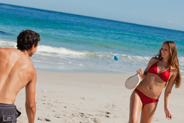 Close-up of a couple playing with beach racket