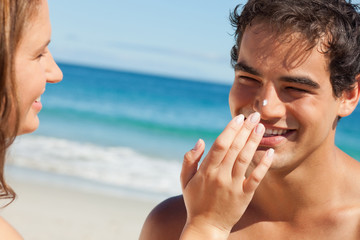 Woman putting some sunscreen on her boyfriend's nose