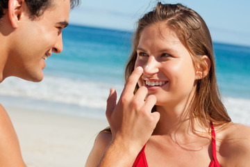 Man putting some sunscreen on his girlfriend's nose