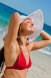 Pretty woman with a hat enjoying the sun