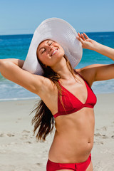 Smiling woman with a hat enjoying the sun