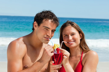 Portrait of a tanned couple drinking a cocktail