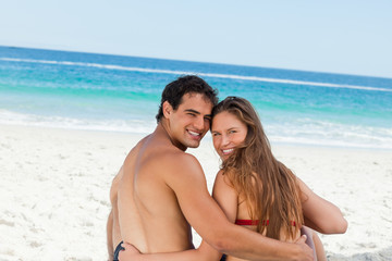 Rear view of a young couple smiling while sitting on the beach