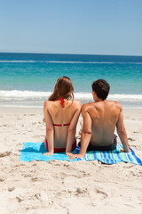 Rear view of a young couple sitting on beach towel