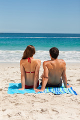 Rear view of a young couple sitting on a beach towel
