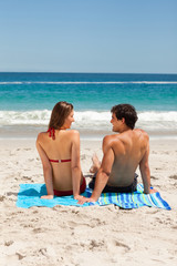 Rear view of a young happy couple sitting on beach towel