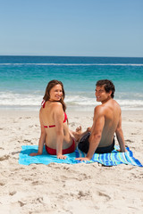 Portrait of a young couple sitting on beach towel