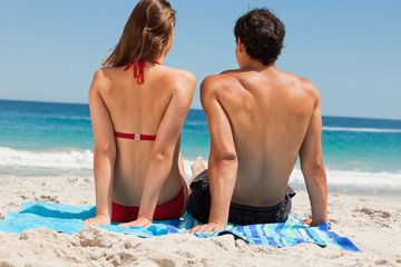 Rear view of a tanned couple sitting on beach towel
