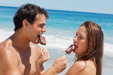 Close-up of lovers eating Popsicle together