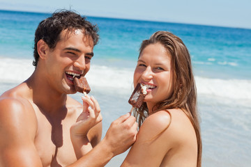 Portrait of lovers eating Popsicle together