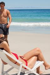 Woman on a deck chair watching her attractive boyfriend
