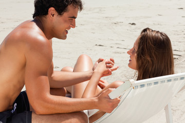 Woman on a deck chair with her tanned boyfriend