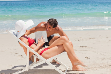 Woman on a deck chair with a book speaking to a man
