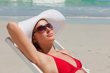 Pretty woman on a deck chair with sunglasses having a sunbath