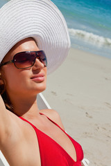 Close-up of a woman on a deck chair with sunglasses having a sunbath