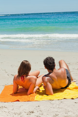 Tanned young lovers lying on the beach