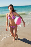 Woman in bikini running while holding a beach ball
