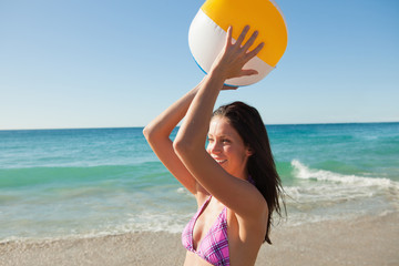 Woman in bikini playing with a beach ball