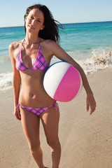 Portrait of a woman in bikini holding a beach ball