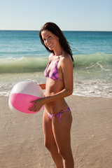 Woman in pink bikini holding a beach ball